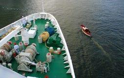Die große Lieferung und das kleine Boot dazu im hohen Meer. Stockbilder