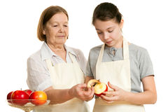 Die Großmutter unterrichtet die Enkelin, eine Schale von abzuschneiden Stockfoto