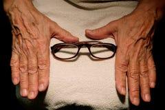 Die Großmutterhände und -gläser für Vision Lizenzfreie Stockfotografie