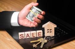 Die Grundstücksmakler ` s Hand hält ein Bündel Geld am Haus mit den Schlüsseln Das Konzept des Kaufens und des Verkaufs von Immob stockfotos