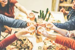 Die Gruppe Freunde, die Abendessen röstend mit Bieren und essend genießen, nehmen Pizza zu Hause - Beifall von den glücklichen Me stockfotos
