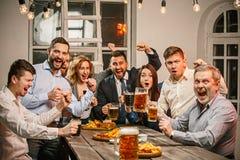 Die Gruppe Freunde, die glättend genießen, trinkt mit Bier lizenzfreies stockfoto