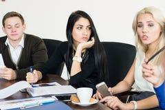Die Gruppe von aktiven Geschäftsleuten bei der Sitzung Stockfotos