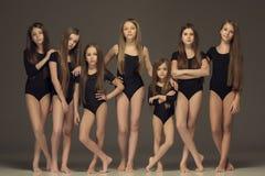 Die Gruppe von den jugendlich Mädchen, die am weißen Studio aufwerfen Lizenzfreies Stockfoto