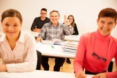 Die Gruppe von Personen des unterschiedlichen Alters sitzend im Klassenzimmer und nehmen teil Lizenzfreies Stockbild