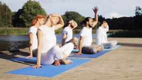 Die Gruppe von Personen, die Yoga macht, trainiert draußen stock video