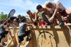 Die Gruppe von Personen springend über ein Hindernis Stockbild