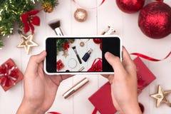 Die Hände, die bewegliches nehmendes Foto von Weihnachten halten, bilden Kosmetik Stockbild