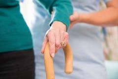 Die Hände der älteren Frau auf Spazierstock-sorgfältig Arbeitskraft in Backgr Lizenzfreie Stockfotos