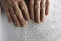 Die Hände der alten Frau, ein Buch mit Blindenschrift-Sprache lesend stockbilder
