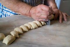 Die Hände der alten Frau, die Teig mit traditionellem Teigschneider schneiden lizenzfreie stockfotografie