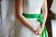 Die Hände der Braut auf einem Hochzeitskleid stockbilder