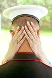 Die Hände der Braut ziehen an sich vom Kopf des Soldaten in der Umarmung zurück Lizenzfreies Stockfoto