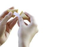 Die Hände der Frau öffnen einen Glückskeks Lizenzfreies Stockbild