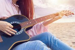 Die Hände der Frau, die Akustikgitarre, Gefangennahmenakkorde durch Finger auf sandigem Strand zur Sonnenuntergangzeit spielen Sp lizenzfreie stockfotos