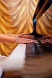 Die Hände der Frau auf der Tastatur des Klaviers Lizenzfreies Stockbild