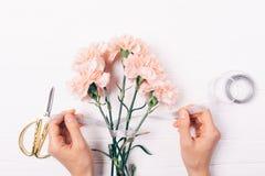 Die Hände der Frau, die Band auf frischen rosa Blumen binden stockbild