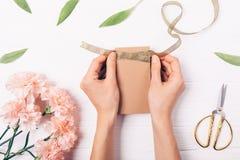 Die Hände der Frau, die braune Geschenkbox mit Band binden lizenzfreie stockfotografie