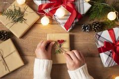 Die Hände der Frau, die den Bogen auf Weinlesegeschenk auf rustikalem Hintergrund binden Festlicher Hintergrund für Winterurlaube lizenzfreies stockbild