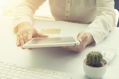 Die Hände der Frau, die eine Kreditkarte halten und intelligentes Telefon für O verwenden Lizenzfreie Stockbilder