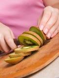 Die Hände der Frau, die frische Kiwi schneiden stockbild