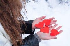 Die Hände der Frau, die geformte Karten des Valentinsgrußherzens halten Stockbild