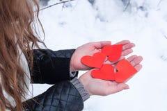 Die Hände der Frau, die geformte Karten des Valentinsgrußherzens halten Stockfotografie