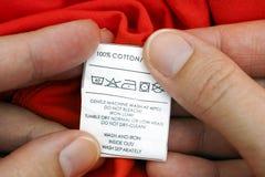 Die Hände der Frau, die Kleidungsaufkleber halten Stockfotografie