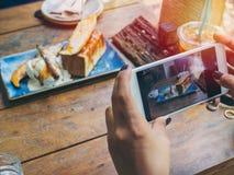 Die Hände der Frau, die Foto des Nachtischs auf Holztisch durch Smartphone machen stockfotografie