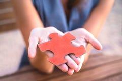Die Hände der Frau halten lebendes korallenrotes Puzzlespiel Nahaufnahme lizenzfreies stockbild