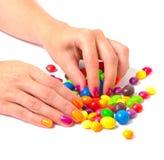 Die Hände der Frau mit der hellen Maniküre, die eine bunte Süßigkeit nimmt Lizenzfreie Stockfotografie