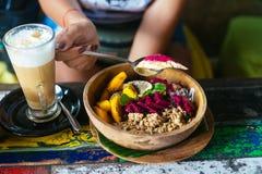 Die Hände der Frau mit der Smoothieschüssel hergestellt mit Mango, Banane, Granola, Kokosraspel, Drachefrucht und Minze mit Latte lizenzfreies stockfoto