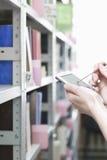 Die Hände der Frau unter Verwendung PDAs in der Bibliothek Stockbilder