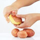 Die Hände der Frauen, die Kartoffeln abziehen lizenzfreie stockfotos