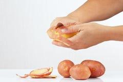 Die Hände der Frauen, die Kartoffeln mit einem Messer abziehen stockfotos