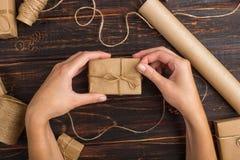Die Hände der Frauen, die ein Geschenk vom Kraftpapier machen Vor dem hintergrund der getrockneten Orange Zimt, Kiefernkegel, Ani lizenzfreie stockbilder