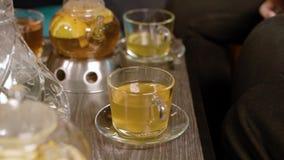 Die Hände der Frauen, die eine Tasse Tee von der Tabelle nehmen stock video footage