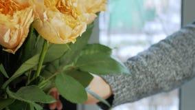 Die Hände der Frauen in einer warmen Strickjackenform ein Blumenstrauß mit den gelben und orange Rosen stock footage