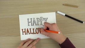 Die Hände der Frauen, die glückliches Halloween-Aufschrift timelapse zeichnen stock footage