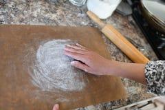 Die Hände der Frauen, die Mehl im Vorbereitungsprozeß für das Backen zubereiten Mädchen, das sich vorbereitet zu backen lizenzfreie stockfotos