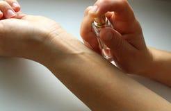 Die Hände der Frauen, die Parfüm auf ihrem Handgelenk spritzen lizenzfreies stockbild