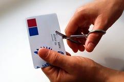Die Hände der Frauen schnitten eine Plastikkarte mit Eisenscheren lizenzfreies stockbild