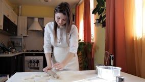 Die Hände der Frauen, die Teig für das Backen mit einem Nudelholz auf einem Leuchtpult rollen stock video