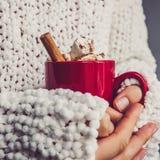 Die Hände der Frauen, weiße Strickjacke und roter Becher lizenzfreie stockfotografie