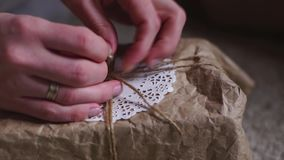 Die Hände der Jungefrau wickeln eine Geschenkbox in der Zeitlupe ein stock video