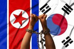 Die Hände der Ketten vor dem hintergrund der Flagge von Nordkorea, DPRK, Südkorea lizenzfreies stockfoto