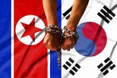 Die Hände der Ketten vor dem hintergrund der Flagge von Nordkorea, DPRK, Südkorea Lizenzfreie Stockfotos