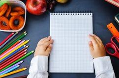Die Hände der Kinder, die Notizbuch auf einer Tafel halten Lizenzfreies Stockfoto