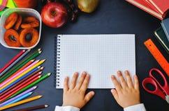 Die Hände der Kinder, die Notizbuch auf einer Tafel halten Lizenzfreies Stockbild
