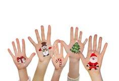Die Hände der Kinder, die oben mit gemalten Weihnachtssymbolen anheben Lizenzfreie Stockfotografie